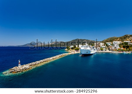 Marmari port with anchored ship against a blue sky and blue waters in Evia, Greece