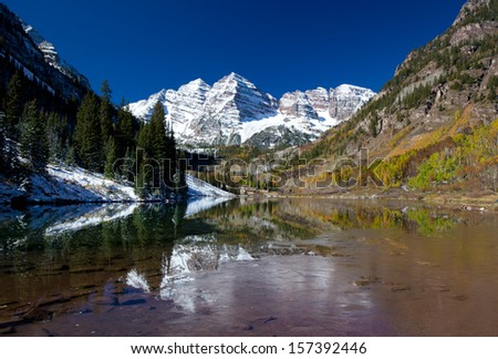 Maroon Bells Lake With Fresh Snow and Autumn Colors - stock photo