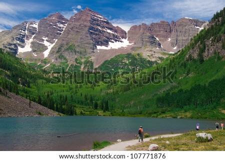Maroon Bells Peaks at Maroon Lake, Summer 2012 with hikers - stock photo