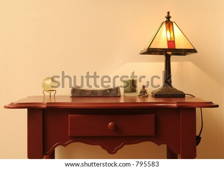 Maroon end table with miscellaneous items