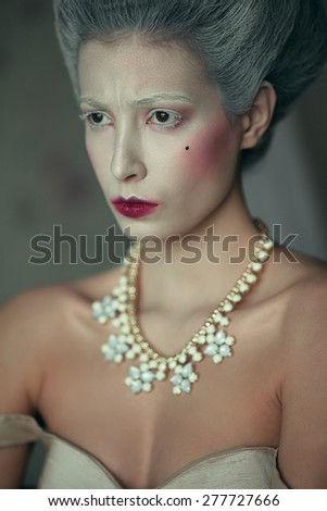 Marquise de Pompadour concept. Vintage emotive portrait of beautiful woman with retro hairdo, luxurious necklace and arty make-up. Rococo style. Close up. Indoor shot - stock photo