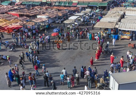 MARRAKECH, MOROCCO - APRIL 23, 2016: Tourists and muslim at Jamaa el Fna (Jemaa el-Fnaa, Djema el-Fna or Djemaa el-Fnaa) square and market place in Marrakesh's medina quarter - stock photo
