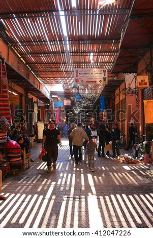 MARRAKECH, MOROCCO - MARCH 23, 2016:  People walking along the pathways of the Souks in Marrakech off of  Place Jemaa el-Fna - stock photo