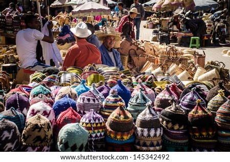 MARRAKECH, MOROCCO- MARCH 19: unidentified people in a traditional street market located in the the Medina of Marrakesh in Morocco on Mar, 19, 2013. They are selling the typical fez, a wool hats.  - stock photo