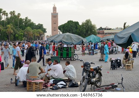 MARRAKESH - JULY 09: Unidentified people siting in Jemaa el Fna Square at sunset, July 09, 2013 in a Marrakesh, Morocco. The square is part of the UNESCO World Heritage - stock photo