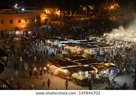 MARRAKESH - JULY 09: Unidentified people visit the Jemaa el Fna Square at dusk, July 09, 2013 in a Marrakesh, Morocco. The square is part of the UNESCO World Heritage. - stock photo