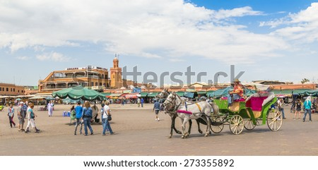 MARRAKESH, MOROCCO, APRIL 3, 2015: Jemaa el-Fnaa square -  Horse drawn carriage waits for tourists  - stock photo