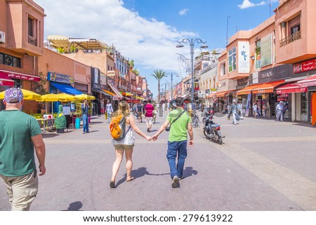 MARRAKESH, MOROCCO, APRIL 3, 2015: Tourists walk on Bab Agnaou street in direction of Jemaa el-Fnaa square - stock photo