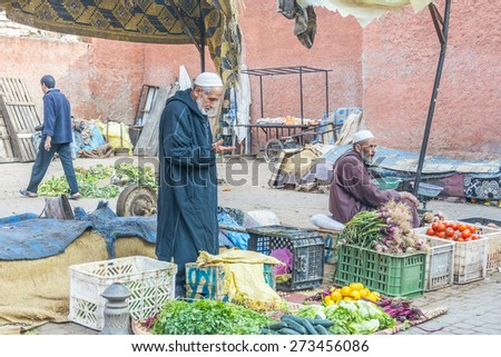 MARRAKESH, MOROCCO, APRIL 4, 2015:  Vendors of greens and vegetables offer their merchandise on street - stock photo