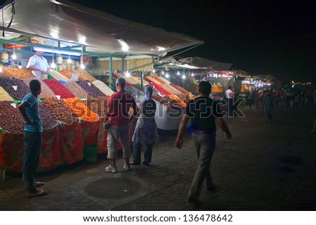 MARRAKESH, MOROCCO - AUG 7: Unidentified people visit stalls with fruit at the Jema el Fna Square in Marrakesh on Aug 7, 2010 in Marrakesh, Morocco. The square is part of the UNESCO World Heritage. - stock photo