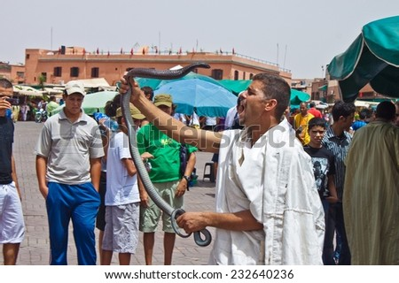 MARRAKESH, MOROCCO - AUGUST 8: Man with a snake at the Jema el Fna Square in Marrakesh on August 8, 2010 in Marrakesh, Morocco. The square is part of the UNESCO World Heritage. - stock photo