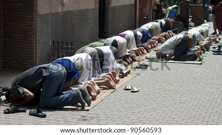 MARRAKESH, MOROCCO - AUGUST 8: Muslim men pray on a street on August 8, 2010 in Marrakesh, Morocco. Islam is the largest religion in Morocco. - stock photo