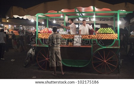 MARRAKESH, MOROCCO - AUGUST 7: Unidentified people visit stalls with juices at the Jema el Fna Square on August 7, 2010 in Marrakesh, Morocco. The square is part of the UNESCO World Heritage. - stock photo