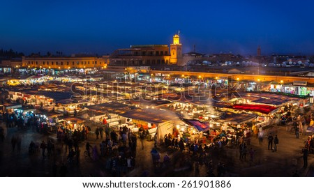 MARRAKESH, MOROCCO- DECEMBER 28: Crowd in Jemaa el Fna square at sunset on December 28, 2014 in Marrakech, Morocco. People blur to imply their movements. - stock photo