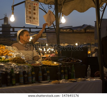 MARRAKESH ,MOROCCO - JUNE 4: Unidentified man selling food at night at the Djemaa el Fna square in Marrakesh on June 4, 2013 in Morocco. Every night the square turns into open air restaurant. - stock photo