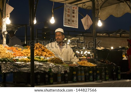MARRAKESH, MOROCCO - JUNE 3: Unidentified man selling orange juicet at night the Jemaa el Fna Square on June 3, 2013 in Marrakesh, Morocco. The square is part of the UNESCO World Heritage. - stock photo