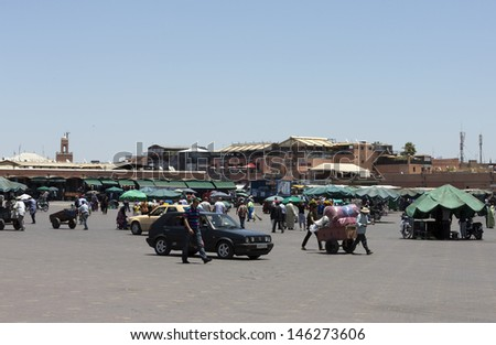 MARRAKESH, MOROCCO - JUNE 3: Unidentified people visit the Jemaa el Fna Square at sunset on June 3, 2013 in Marrakesh, Morocco. The square is part of the UNESCO World Heritage.  - stock photo
