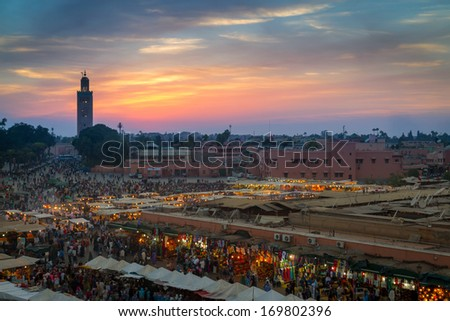 MARRAKESH, MOROCCO - NOVEMBER 7: Many people visit the Jemaa el Fna Square at sunset on November 7, 2013 in Marrakesh, Morocco. This square is part of the UNESCO World Heritage.  - stock photo