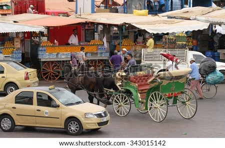 MARRAKESH, MOROCCO - OCTOBER 8: A traditional horse and carriage and a taxi in the Jemaa el Fna Square in Marrakesh, Morocco on the 8th October, 2015. - stock photo