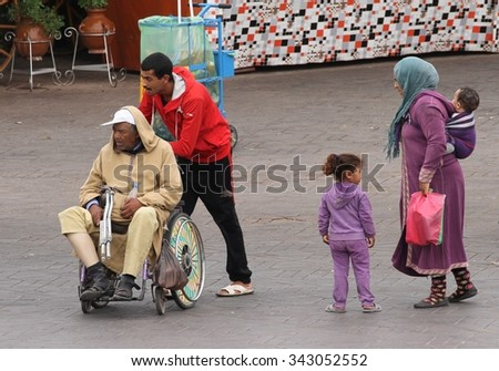 MARRAKESH, MOROCCO - OCTOBER 8: An elderly man being pushed in a wheelchair with his family in Jemaa el Fnaa Square, Marrakesh, Morocco on the 8th October, 2015. - stock photo