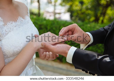 marriage hands with rings. groom wears the ring on the finger of the bride at the green background
