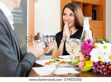 Marriage proposal. Man presenting to amazed woman engagement ring at table  in home - stock photo