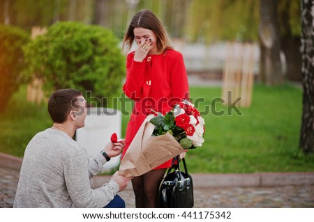 Marriage proposal. Man with boquet of flowers kneeling and give engagement ring for his girlfriend - stock photo