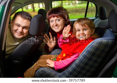 Married couple and  little girl  Greeting to wave hands in car in park - stock photo
