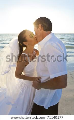 Married couple, bride and groom, kissing at sunset on a beautiful tropical beach wedding - stock photo