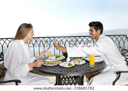 Married Couple enjoying breakfast on hotel terrace - stock photo