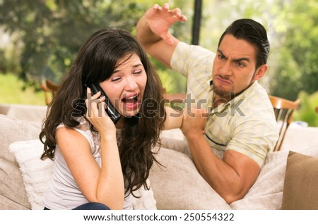 married couple fighting having an argument at home wife calling for help concept of domestic violence - stock photo
