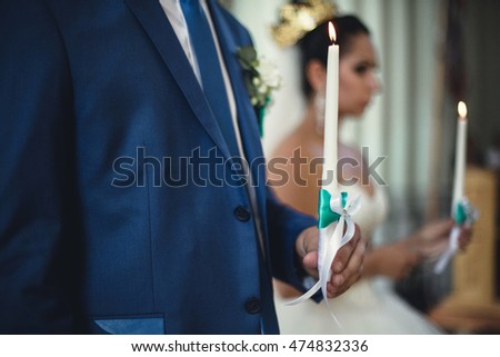 married couple holding candles in church
