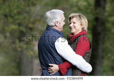 Married couple hugging in park - stock photo