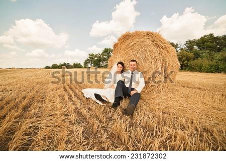 married couple sitting near haystack on summer field - stock photo