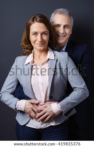 Married couple wearing business casual clothing and stand one behind the other as the man holds his wife around the waist - stock photo