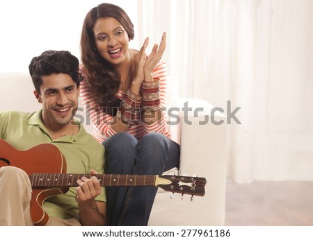 Married couple with guitar - stock photo