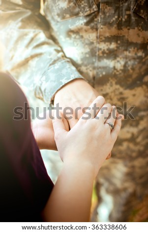Married military couple holding hands - stock photo