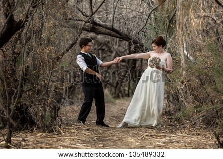 Married same sex couple dancing in the forest together