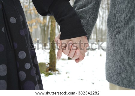 Married young loving couple holding hands each other in park, face is not visible.Couple holding hands and walking in park.hands holding together,  - stock photo