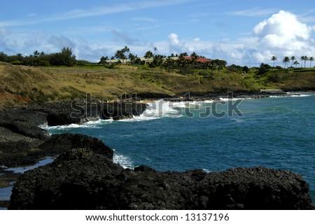 Marriott Kauai Lagoons golf course faces the beautiful blue ocean.  Steep rugged cliffs.  Blue sky. - stock photo