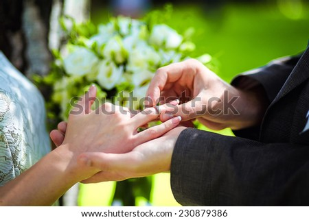 Marry me. Groom put a ring on finger of his lovely wife. Wedding couple together. - stock photo