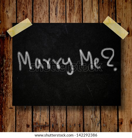 Marry me on message note with wooden background - stock photo
