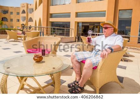 MARSA ALAM, EGYPT, MARCH 28, 2016:  Senior tourist enjoys a drink on Three Corners Equinox Beach Hotel terrace in Marsa Alam, Egypt - stock photo