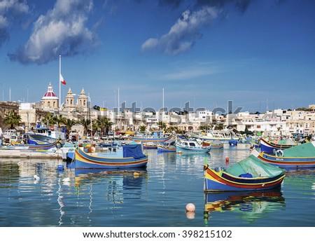 marsaxlokk harbour and traditional mediterranean fishing boats in malta island - stock photo