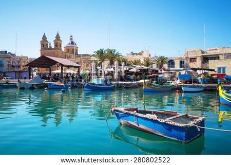 Marsaxlokk market with traditional colorful fishing boats, Malta - stock photo