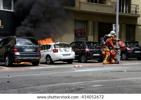 Marseille, France - April 28, 2016 : Firefighters extinguishing a car fire burned during clashes between protesters and french riot police during a demonstration against the labor law - stock photo