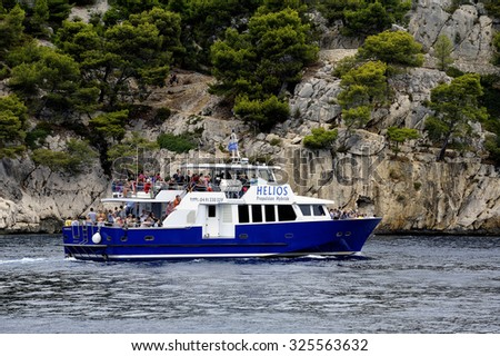 MARSEILLE, FRANCE - SEPTEMBER 4: Tourists on boat along the creeks of Marseille to discover the beautiful landscapes of the National Park under gray skies, September 4, 2015. - stock photo
