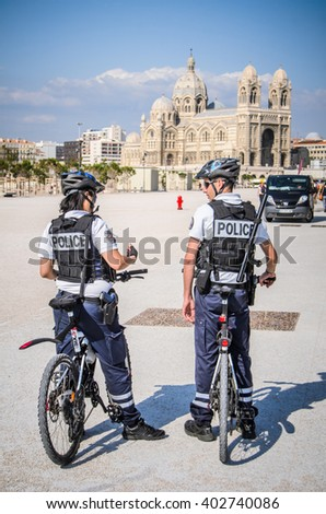 MARSEILLES, FRANCE - MAY 7 2014: Two French police officers on bikes in front of Marseilles Cathedral - stock photo