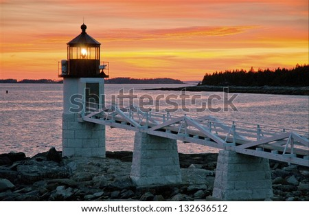 Marshall Point Lighthouse, located in Port Clyde, has some of the most dramatic sunsets in Maine. - stock photo