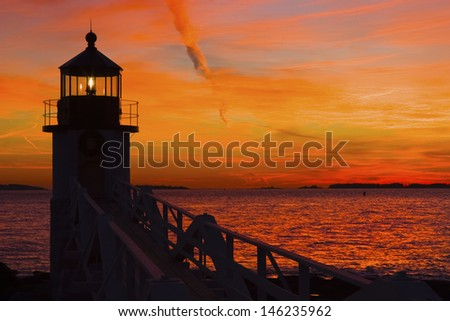 Marshall Point Lighthouse with orange sky at sunset on the coast of Maine. - stock photo